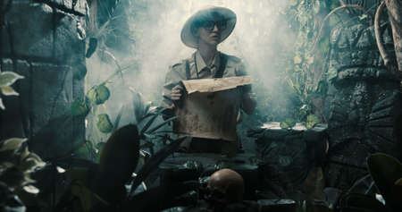Scared explorer lost in the jungle: she is holding a map and looking at some ancient ruins