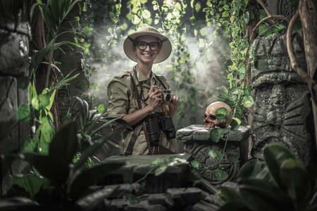 Brave woman exploring the jungle and taking pictures with her camera, she finds ancient ruins and a human skull