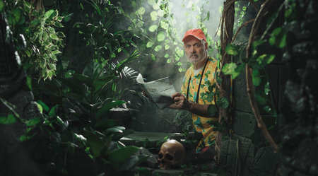 Funny scared tourist lost in the tropical jungle, he is holding a map