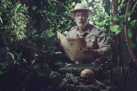 Vintage explorer holding an ancient map and walking in the forest