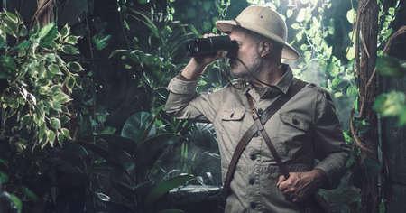 Brave explorer walking alone in the jungle he is looking through binoculars
