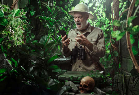 Angry explorer using his smartphone in the jungle, he is unable to connect because there is no network coverage