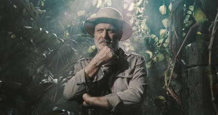 Brave explorer in the tropical jungle, he is thinking with hand on chin