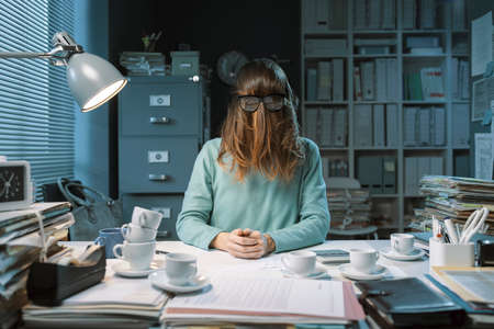Insane office worker covering her face with hair and wearing glasses, workplace burnout concept Stockfoto