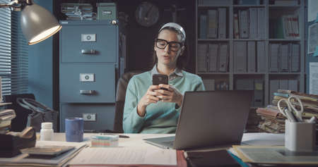 Inefficient office worker sitting at desk and chatting with her phone instead of working Stockfoto
