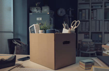 Office worker belongings in a carton box: job dismissal and crisis concept