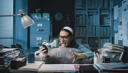 Stressed office worker waking up in the office, she is holding the alarm clock and shouting