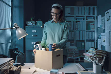 Sad woman packing her belongings in the office after being fired Stockfoto