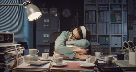 Exhausted office worker falling asleep in the office late at night after drinking too much coffee Stockfoto