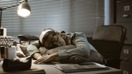 Exhausted young office worker sleeping at her desk, job burnout and overtime work concept