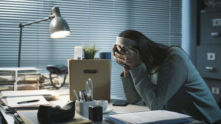 Desperate woman packing her belongings and crying after losing her job Stockfoto