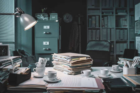 Pile of paperwork and coffee cups on the office desk: deadlines and stressful job concept