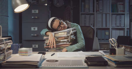 Exhausted office worker sleeping at desk and leaning on a pile of paperwork: overtime work and deadlines concept