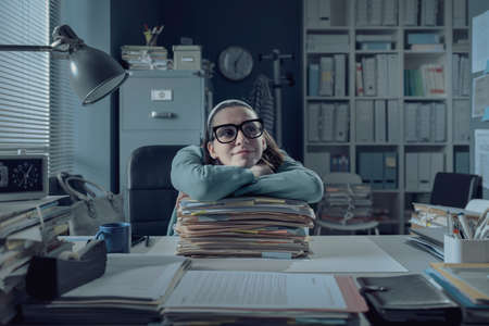 Lazy office worker sitting at desk and leaning on a pile of paperwork, she is smiling and looking away Stockfoto