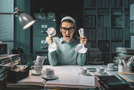 Stressed angry employee working late at night, she is shouting and crumpling paper sheets