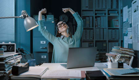 Happy relaxed woman sitting at desk in the office and stretching her arms Stockfoto