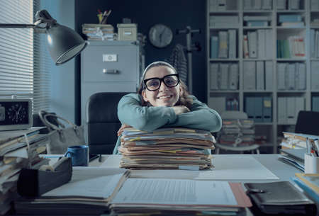 Lazy office worker sitting at desk and leaning on a pile of paperwork, she is smiling and looking at camera