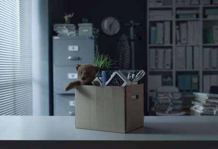 Cardboard box filled with employee's personal belongings: job dismissal and relocation concept Stockfoto