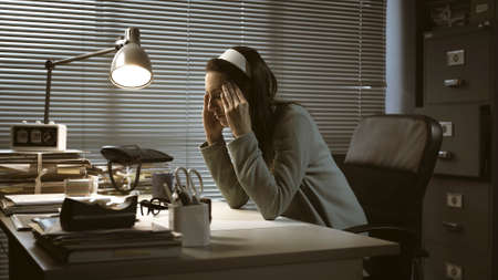 Stressed businesswoman sitting at desk and having a bad headache, job burnout concept Stockfoto