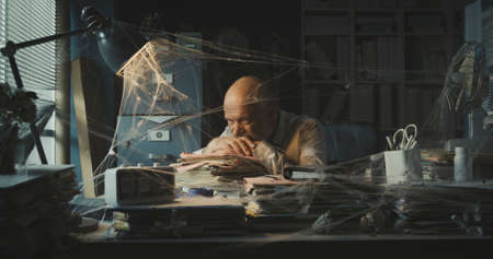 Corporate businessman dealing with business failure, he is sitting at desk in his dusty abandoned office Stockfoto