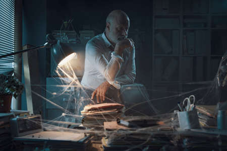 Frustrated pensive businessman in his abandoned office: closing a business and financial crisis concept Stockfoto