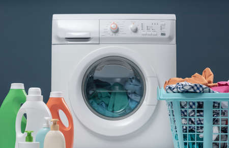 Washing machine, laundry basket with clothes and set of detergents Foto de archivo