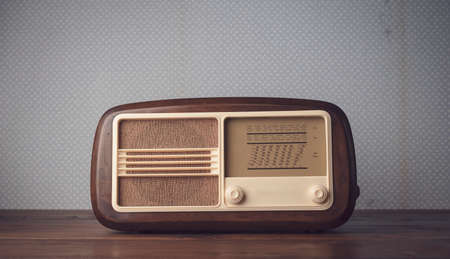Vintage radio on the table and vintage wallpaper: music and entertainment concept, blank copy space