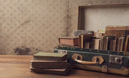 Old suitcase full of vintage books and novels, reading and travel concept
