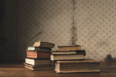Vintage books stack on old wooden surface Stock Photo