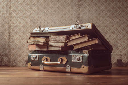Vintage suitcase full of old books and novels, travel and reading concept