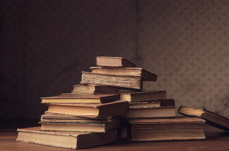 Heap of old hardcover books on a desk and vintage wallpaper Stock Photo
