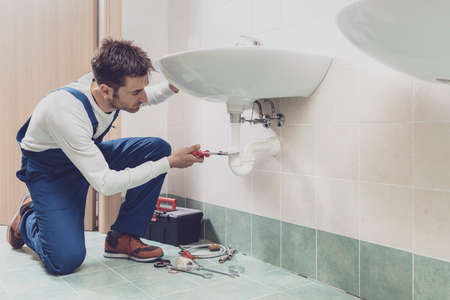 Professional plumber installing or fixing a sink at home