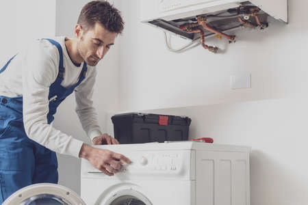 Repairman fixing a washing machine, he is adjusting a knob, professional service concept Stock fotó