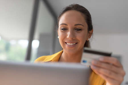 Smiling woman connecting with her laptop and doing online shopping with her credit card