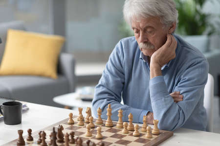 Focused senior man playing chess, he is looking at the chessboard and thinking