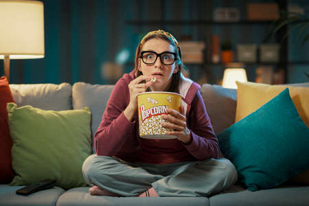 Woman watching a suspense movie and eating popcorn