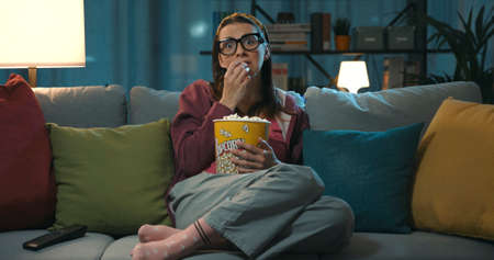 Woman watching television and eating popcorn, she is sitting on the sofa at home and staring at the TV screen