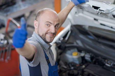 Smiling mechanic giving a thumbs up after checking the car 版權商用圖片
