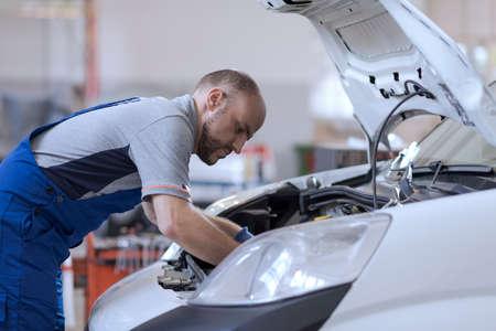 Professional mechanic checking a car engine, car repair service concept