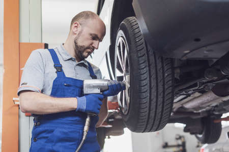 Professional mechanic doing a wheel replacement on a lifted car using a pneumatic wrench