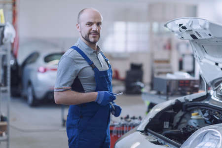 Confident mechanic posing in the garage, he is checking a car engine 版權商用圖片