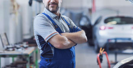 Mechanic posing in the auto repair shop, car service and assistance concept 版權商用圖片