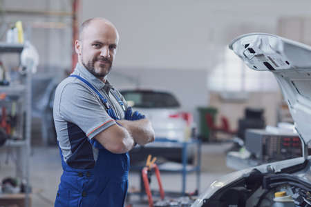 Professional mechanic posing in the workshop next aa car, auto repair and assistance concept