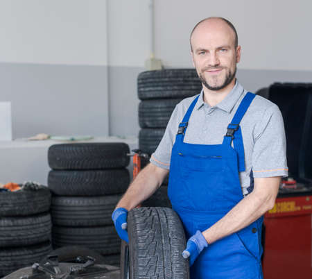 Professional smiling mechanic posing in the auto repair station, he is holding a tire