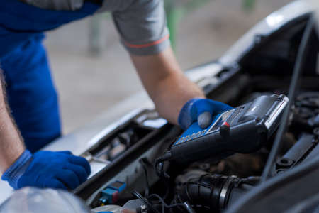 Professional mechanic doing a car inspection, he is using a battery tester