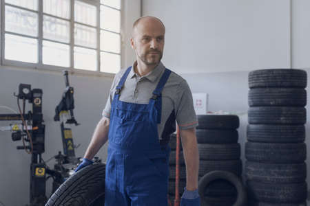 Professional mechanic working in the auto repair station, he is carrying a tire