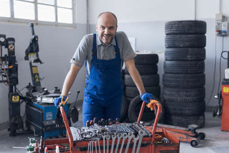 Mechanic working in the auto repair shop, he is leaning on a tool cart and smiling