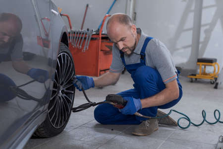 Mechanic inflating a tire and checking air pressure with a pressure gauge at the auto repair shop 版權商用圖片