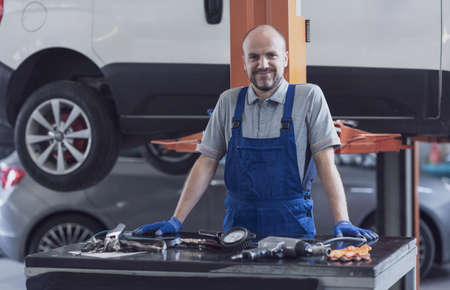 Smiling mechanic posing in the auto repair shop, car service and repair concept
