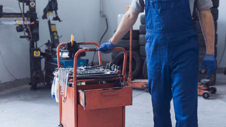 Mechanic working in the auto repair shop, he is pulling a tool cart